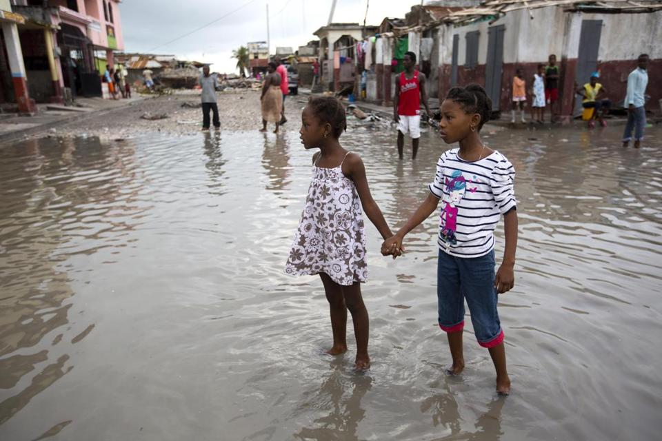 Two girls held hands while traversing a flooded street in Les Cayes, Haiti, after Hurricane Matthew.