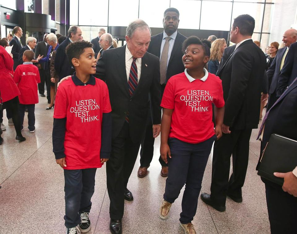Boston/Cambridge, MA--10/18/2016--After the unveiling of name of the William and Charlotte Bloomberg Science Education Center (cq), Michael R. Bloomberg (cq) walks through the Museum of Science, to a luncheon, with Nathan Hale School students Aliaahn Rafique (cq), 10, left, and Vanessa Paige (cq), 10. Bloomberg and Bloomberg Philanthropies (cq) announce a gift to the Museum of Science, on Tuesday, October 18, 2016. Photo by Topic: 19bloomberg Reporter: XXX