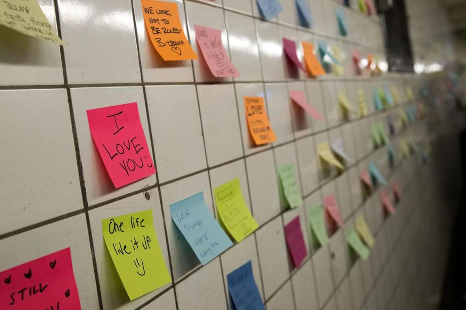 Notes, many with politically themed messages, hang on a wall at the 6th Avenue subway station.