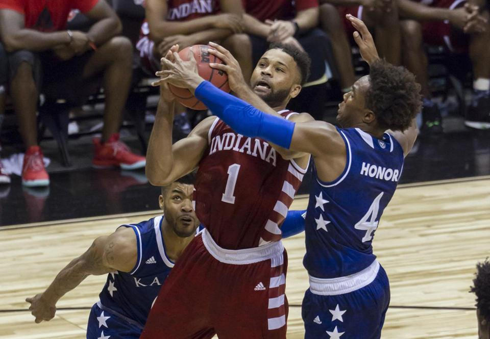 Indiana guard James Blackmon Jr. (1) attempts a layup while being defended by Kansas guard Frank Mason III, left, and guard Devonte' Graham (4) during the second half of an NCAA college basketball game at the Armed Forces Classic, Friday, Nov. 11, 2016, in Honolulu. Indiana won 103-99 in overtime. (AP Photo/Eugene Tanner)