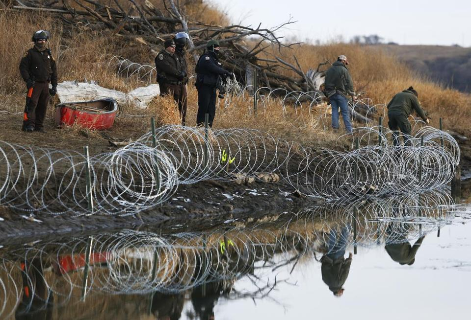 Police adjusted barbed wire that they set up on Turtle Island a day after protesters built a bridge to access it in Cannon Ball, N.D,