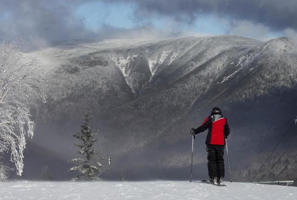 A skier looks out over the White Mountains before skiing on opening day at Loon Mountain ski resort Wednesday, Nov. 23, 2016, in Lincoln,N.H. Many ski areas in Northern New England plan to open for the Thanksgiving weekend. (AP Photo/Jim Cole)