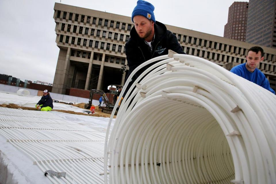 "Nick Norris  and Scott Grealish of Ice Rink Events rolled tubing for the skating path ahead of the opening of ""Boston Winter"" at City Hall Plaza. Antifreeze is used in the tubing to freeze the water."