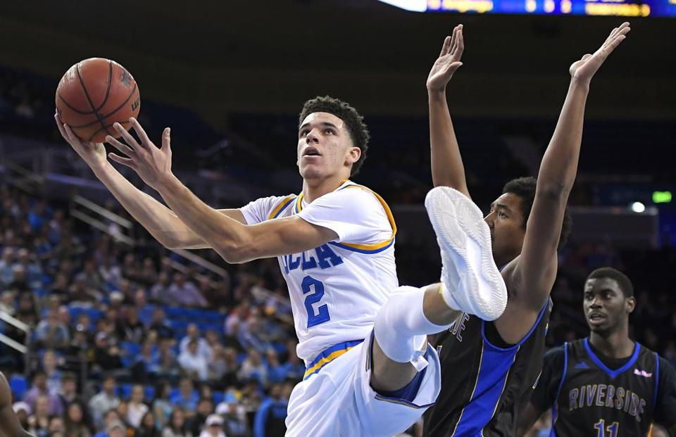 UCLA guard Lonzo Ball, left, shoots as UC Riverside forward Brandon Rosser defends during the second half of an NCAA college basketball game Wednesday, Nov. 30, 2016, in Los Angeles. UCLA won 98-56. (AP Photo/Mark J. Terrill)