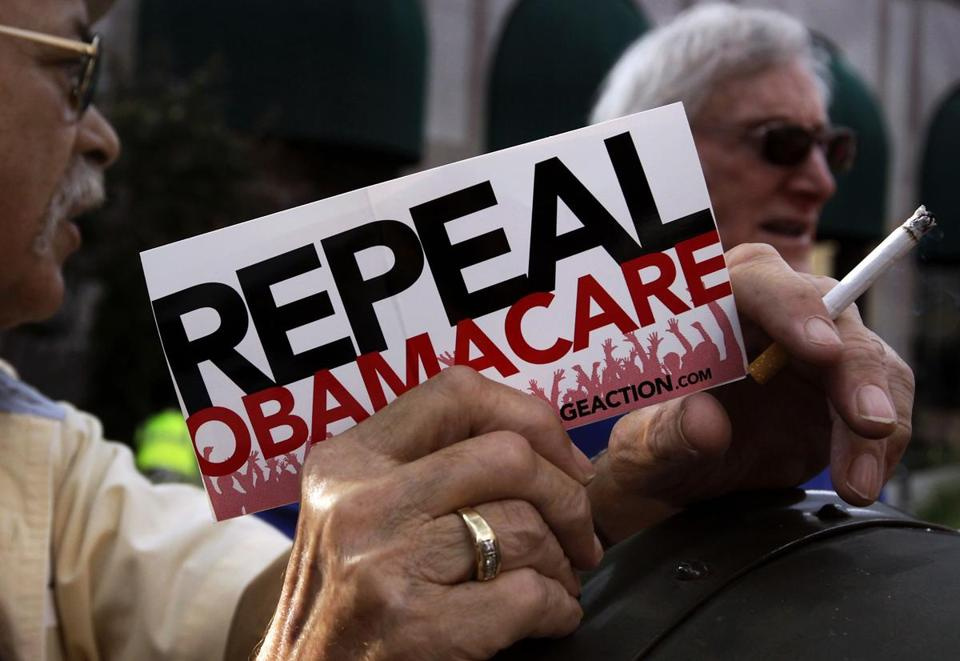"A small group of demonstrators stand outside of of a hotel before former South Carolina Senator Jim DeMint, president of the The Heritage Foundation, speaks at a ""Defund Obamacare Tour"" rally in Indianapolis, Indiana, U.S. August 26, 2013. REUTERS/Nate Chute/File Photo"