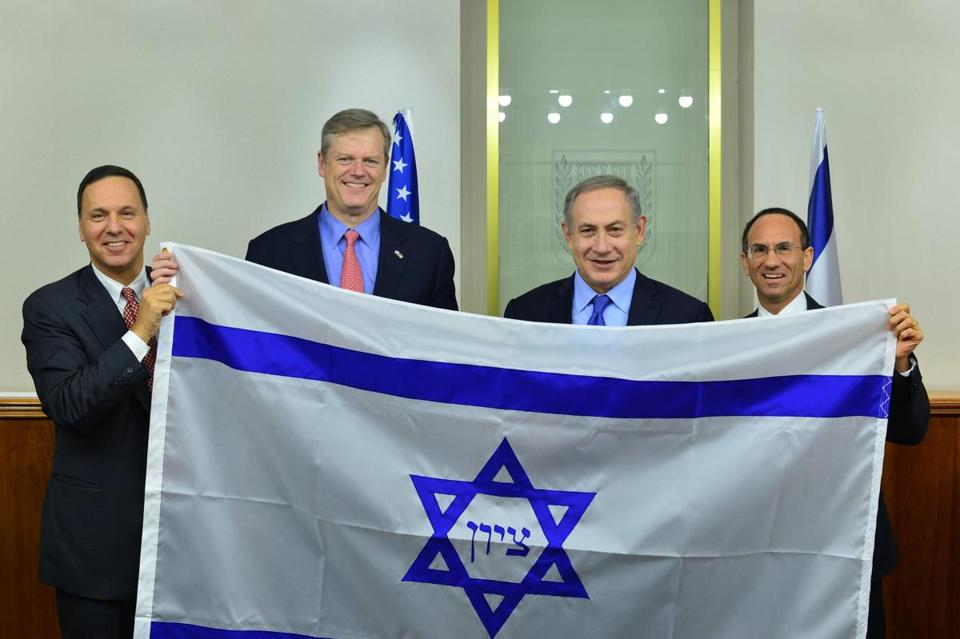 Brandeis president Ron Liebowitz, Governor Charlie Baker, Israeli Prime Minister Benjamin Netanyahu, and Consul General of Israel to New England Yehuda Yaakov with a replica of an 1890s flag from Boston.