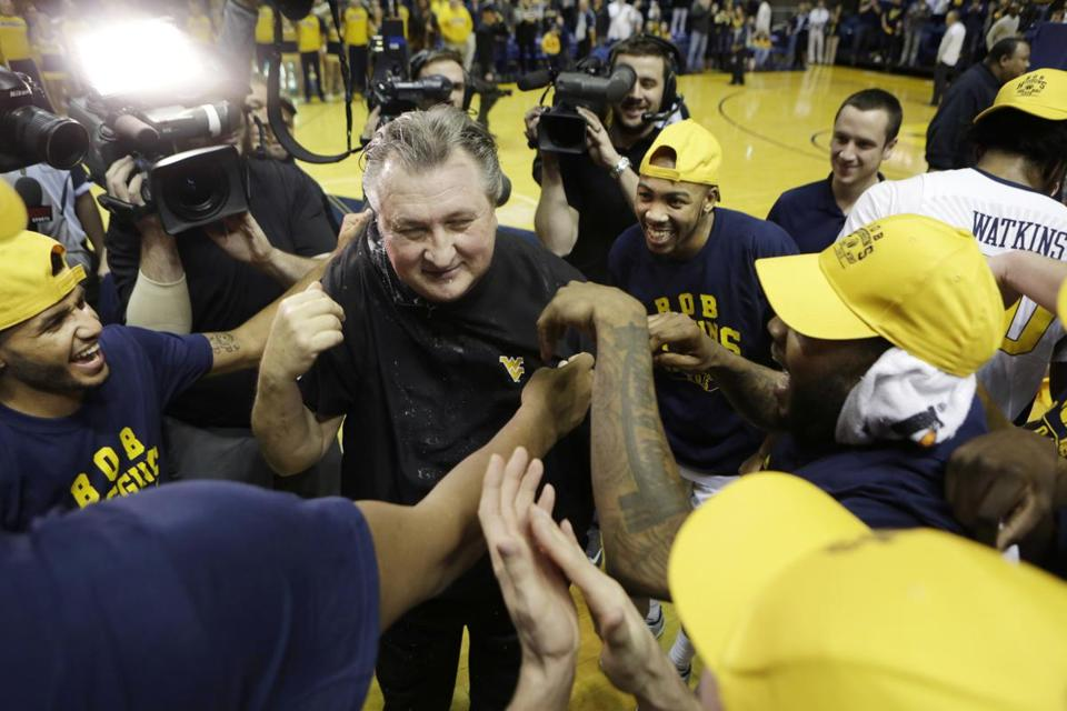 West Virginia head coach Bob Huggins celebrates his 800th career win at the conclusion of an NCAA college basketball game against UMKC, Saturday, Dec. 17, 2016, in Morgantown, W.Va. West Virginia defeated UMKC 112-67. (AP Photo/Raymond Thompson)