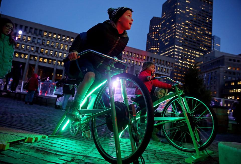 "Boston, MA - December 21, 2016: Brandon Comeau (cq) , 10, of Rockland, pedals a stationary bike to light a Christmas tree at ""Boston Winter presented by Berkshire Bank"" at City Hall Plaza in Boston, MA on December 21, 2016. The venue includes a 11,000-square-foot Skating Path and The Chocolate Story, and a 20-foot tall pedal-powered holiday tree that lets up to four people work together to ""pedal"" the lights up to the very top. (Craig F. Walker/The Boston Globe) Section: Metro reporter:"