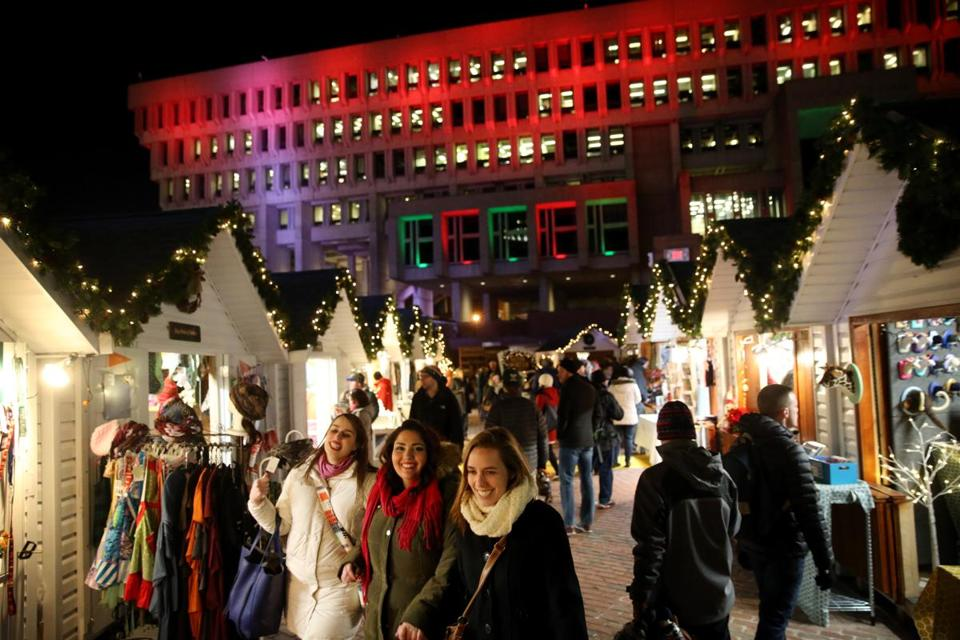 "Boston, MA - December 21, 2016: Visitor pass the ""chalets"" as the enter ""Boston Winter presented by Berkshire Bank"" at City Hall Plaza in Boston, MA on December 21, 2016. The venue includes a 11,000-square-foot Skating Path and The Chocolate Story, and a 20-foot tall pedal-powered holiday tree that lets up to four people work together to ""pedal"" the lights up to the very top. (Craig F. Walker/The Boston Globe) Section: Metro reporter:"