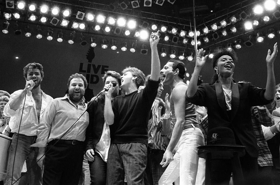 In July 1985, George Michael (left) of Wham!, Harvey Goldsmith, Bono of U2, Paul McCartney, Bob Geldof, and Freddie Mercury of Queen joined in the finale of the Live Aid famine relief concert in London.