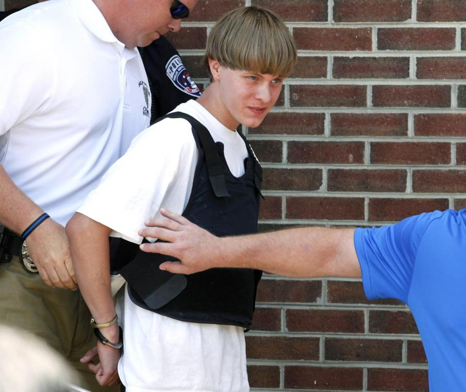 Police lead suspected shooter Dylann Roof into the courthouse in Shelby, North Carolina, June 18, 2015. Roof, a 21-year-old with a criminal record, is accused of killing nine people at a Bible-study meeting in a historic African-American church in Charleston, South Carolina, in an attack U.S. officials are investigating as a hate crime. REUTERS/Jason Miczek