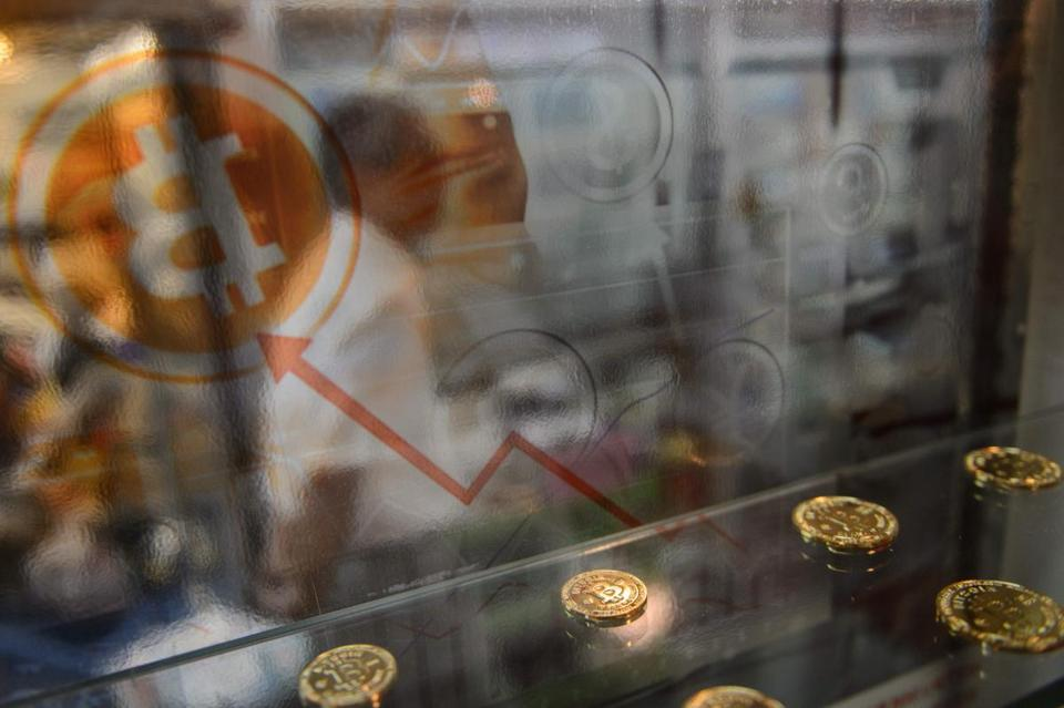 A man walked past a display cabinet containing models of Bitcoins in Hong Kong.