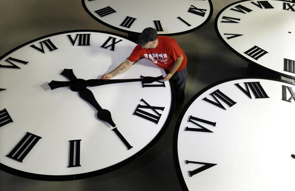 In this Thursday, Nov. 3, 2016 photo, Dan LaMoore sizes hands for an 8-foot diameter silhouette clock at Electric Time Co., in Medfield, Mass. Daylight saving time ends at 2 a.m. local time Sunday, when clocks are set back one hour. (AP Photo/Elise Amendola)