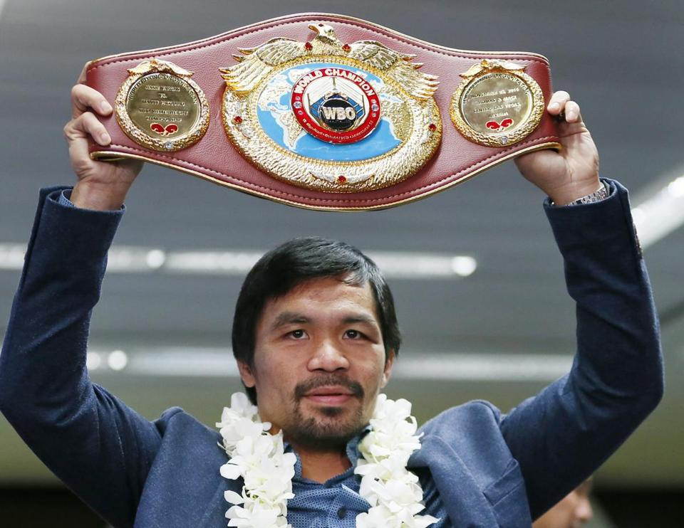 FILE - In this Tuesday, Nov. 8, 2016, file photo, Filipino boxer Manny Pacquiao raises his WBO welterweight championship belt during a news conference upon arrival at the Ninoy Aquino International Airport in Pasay city, southeast of Manila, Philippines. Pacquiao, 38, will add another fight to his long career resume when he takes on Australian welterweight Jeff Horn on April 23 at a venue to be decided. (AP Photo/Bullit Marquez, File)