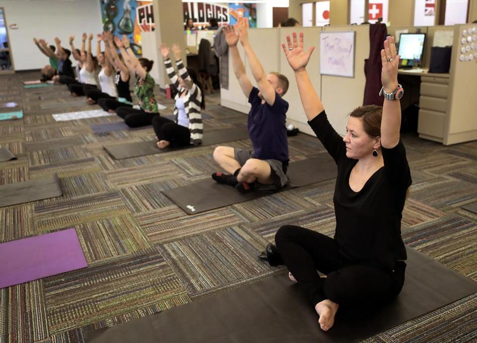 QUINCY, MA - 1/18/2017: CEO Megan Driscoll (on the right ) in a yoga class at PharmaLogics Recruiters in Quincy.... PharmaLogics Recruiters in Quincy raised base pay a year ago from $37k to $50k for 35 out of their 48 employees. (David L Ryan/Globe Staff Photo) SECTION: BUSINESS TOPIC 20pharmalogics