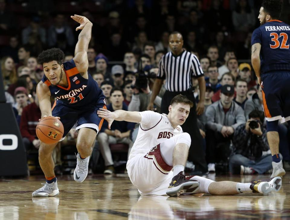 Boston College forward Nik Popovic (21) reaches out to Virginia forward Isaiah Wilkins (21), who recovers a turnover during the first half of an NCAA college basketball game in Boston, Wednesday, Jan. 18, 2017. (AP Photo/Mary Schwalm)