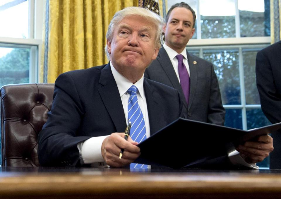TOPSHOT - US President Donald Trump signs an executive order as Chief of Staff Reince Priebus looks on in the Oval Office of the White House in Washington, DC, January 23, 2017. Trump on Monday signed three orders on withdrawing the US from the Trans-Pacific Partnership trade deal, freezing the hiring of federal workers and hitting foreign NGOs that help with abortion. / AFP PHOTO / SAUL LOEBSAUL LOEB/AFP/Getty Images