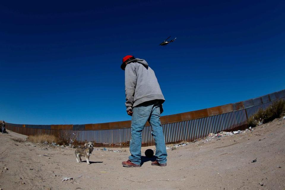 epa05753151 A man plays with his dog near to the border fence between Anapra, in Ciudad Juarez, Mexico, and the US states of Texas and New Mexico, 26 January 2017. Mexican President Enrique Peña Nieto cancelled his proposed trip to the USA, on 26 January due to President Donald J. Trump's insistence on building a wall on the USA/Mexico border, and his claims that 'Mexico will pay for the wall.' On 25 January, President Trump signed an executive order to begin 'immediate construction' of the controversial border wall. EPA/Alejandro Bringas