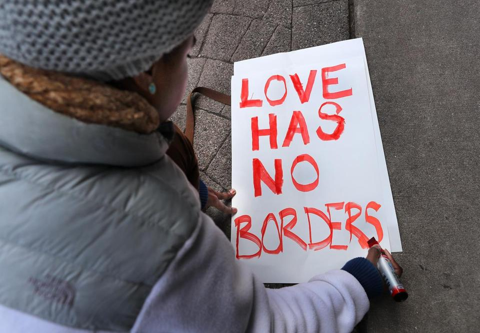 Tori Furtado wrote a sign for a Boston rally that protested President Donald Trump's immigration policies on Saturday.