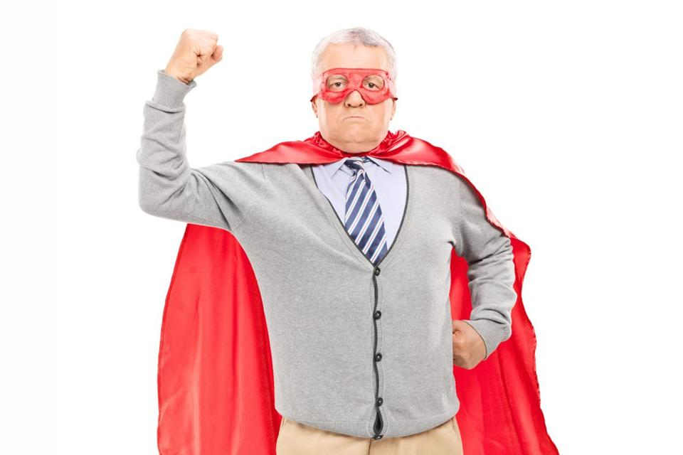 Proud mature man in superhero costume throwing his fist in the air isolated on white background