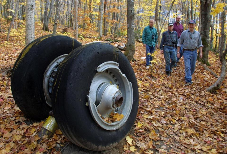 Bob, Nelson, left to right, Dave Perry, Mike Wagner and Douglas Wagner walk past a landing gear from B-52 Stratofortress that crashed in Greenville, Maine in January 1963 during a test flight. A local group, the Moosehead Riders Snowmobile Club, has been doing work to the trail that leads to the site to make it more accessible to visitors. Library Tag 10212001 METRO