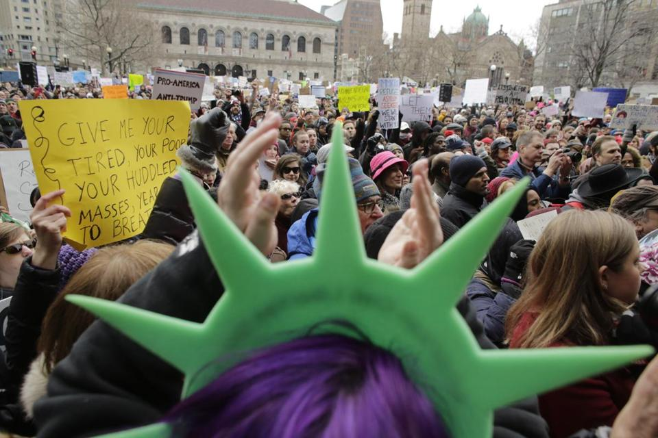 A demonstrator wore a Statue of Liberty hat and clapped during a rally in Boston.