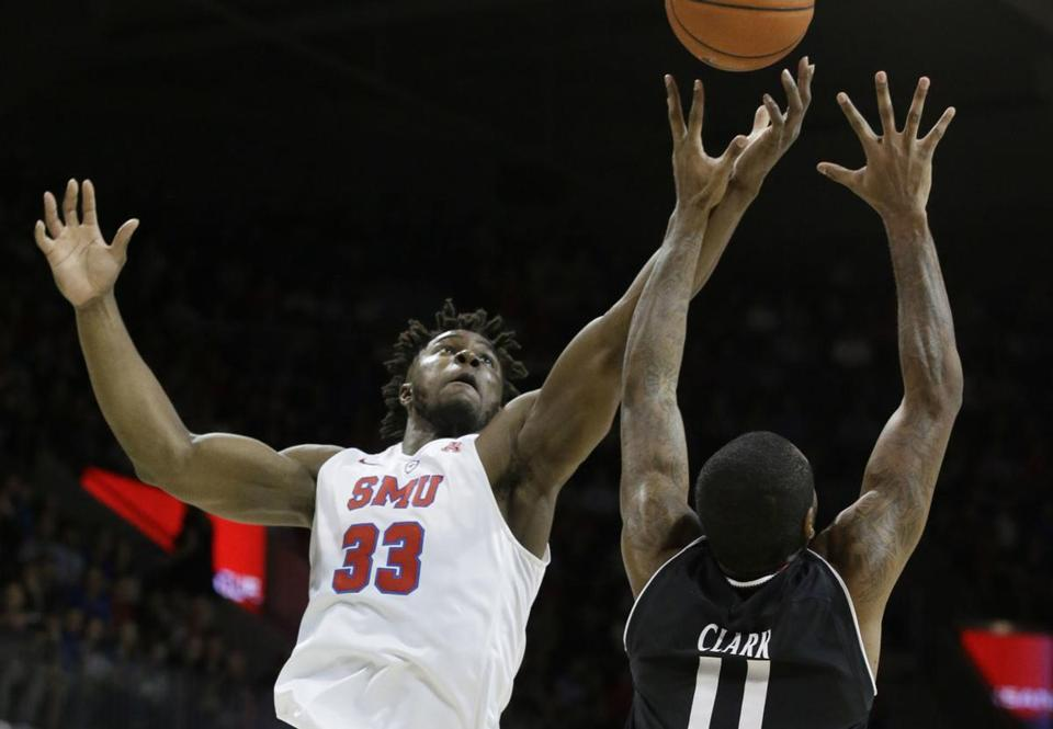 SMU forward Semi Ojeleye (33) reaches for a rebound against Cincinnati forward Gary Clark (11) during the first half of an NCAA college basketball game in Dallas, Sunday, Feb. 12, 2017. (AP Photo/LM Otero)
