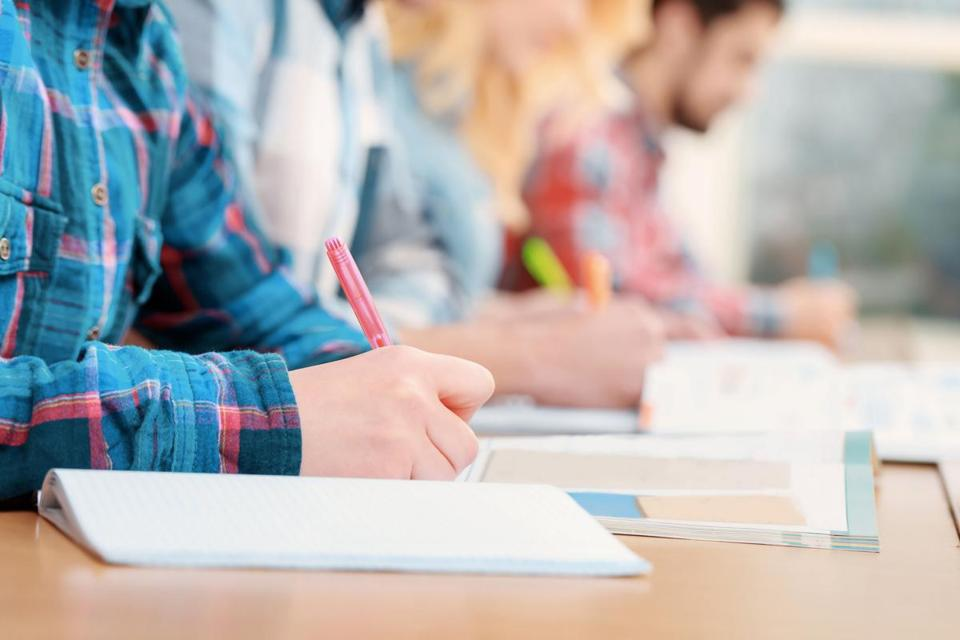 Exams. Cropped view of students writing a test in their exercise books