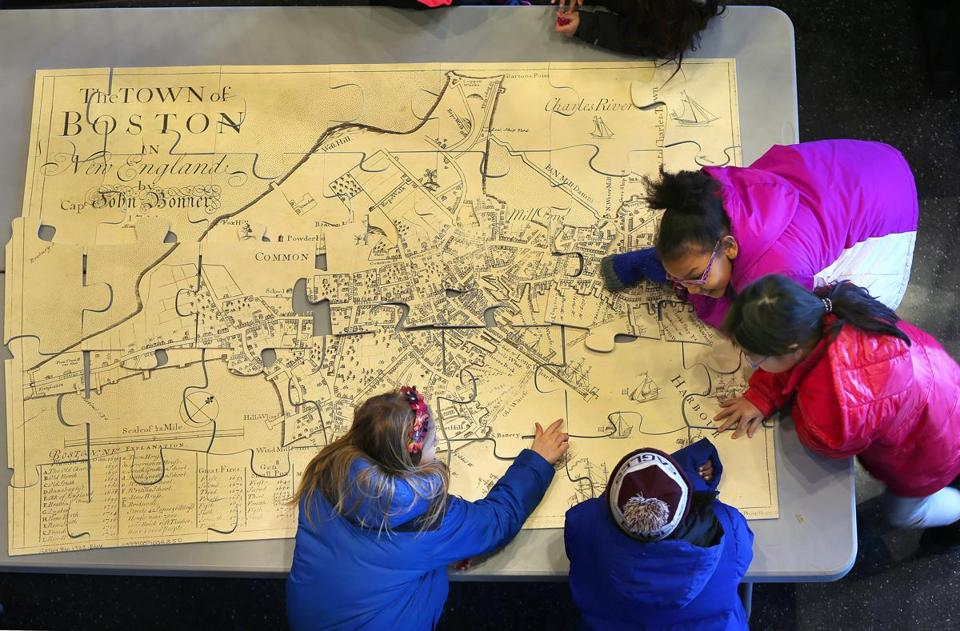 Students put together a puzzle of an old map of Boston at Boston Public School headquarters in Dudley Square.