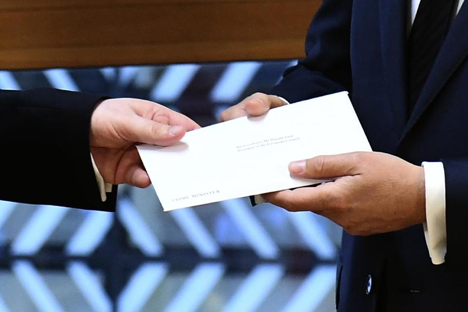 EU Council President Donald Tusk gets British Prime Minister Theresa May's formal notice from UK Permanent Representative to the EU Tim Barrow in Brussels, Wednesday, March 29, 2017. Barrow hand-delivered the letter signed by Britain's Prime Minister Theresa May that will formally trigger the beginning of Britain's exit from the European Union. (Emmanuel Dunand, Pool via AP)