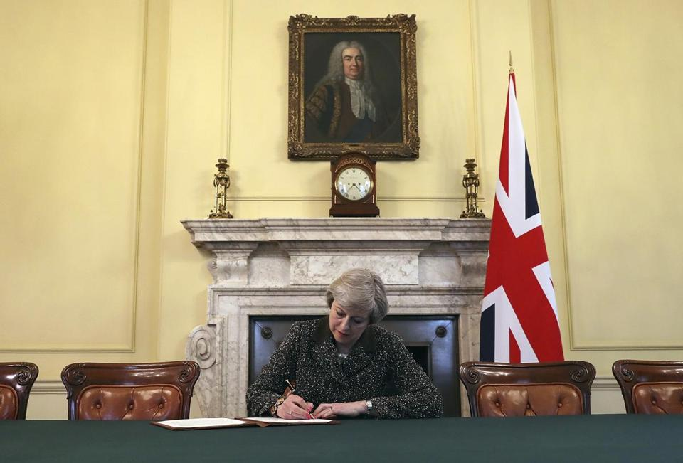 Britain's Prime Minister Theresa May, sitting below a painting of Britain's first Prime Minister Robert Walpole, signs the official letter to European Council President Donald Tusk, in 10 Downing Street, London, Tuesday March 28, 2017, invoking Article 50 of the bloc's key treaty, the formal start of exit negotiations. Britons voted in June to leave the bloc after four decades of membership. (Christopher Furlong/Pool Photo via AP)