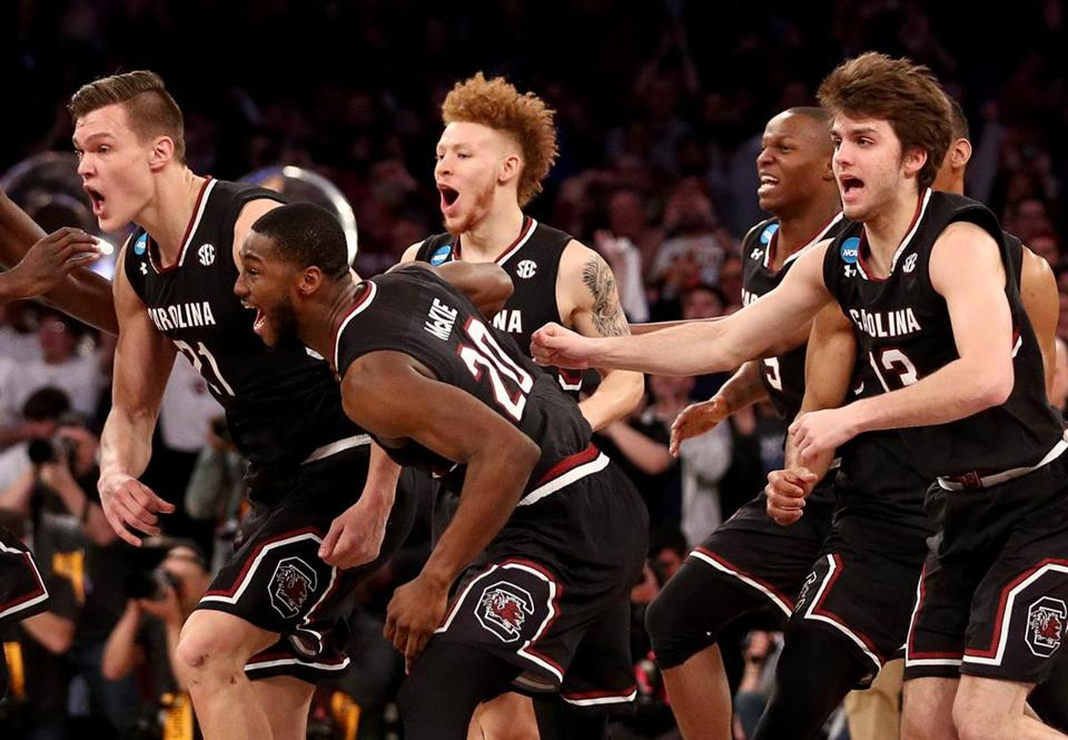 NEW YORK, NY - MARCH 26: Maik Kotsar #21 and Justin McKie #20 of the South Carolina Gamecocks celebrate with their teammates after defeating the Florida Gators with a score of 77 to 70 to win the 2017 NCAA Men's Basketball Tournament East Regional at Madison Square Garden on March 26, 2017 in New York City. (Photo by Maddie Meyer/Getty Images)