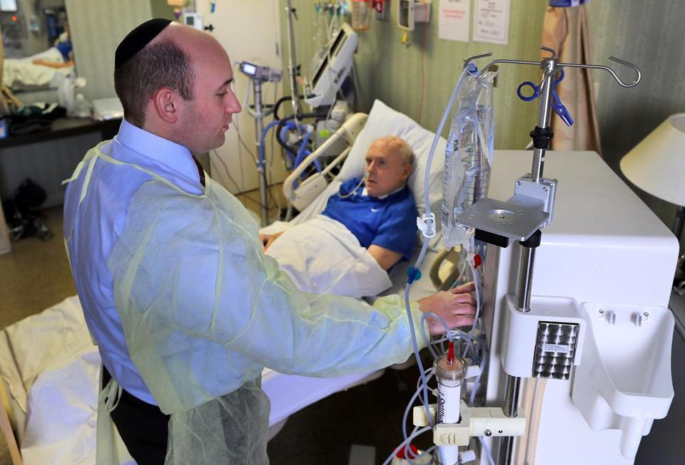 At Hebrew Senior Life, Dr. Ernest Mandel prepared to administer dialysis to patient John Glynn.