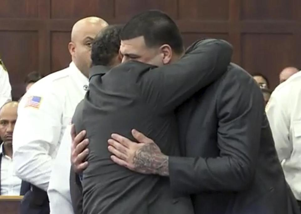 In this still image from video, Aaron Hernandez, center, is hugged by defense attorney Ronald Sullivan on Friday.