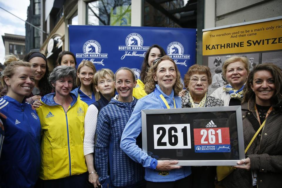 Boston, Massachusetts -- 4/18/2017 - Kathrine Switzer poses for a portrait with members of the B.A.A. following a ceremony held to retire her bib number 261 at Boston Marathon adidas Runbase. (Jessica Rinaldi/Globe Staff) Topic: Boston Marathon Reporter: