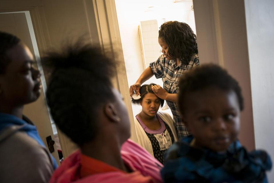 Kimberly Donald combed the hair of her daughter Janell Brooks in Racine, Wis. Donald said she's doubtful the program would accurately identify drug users.