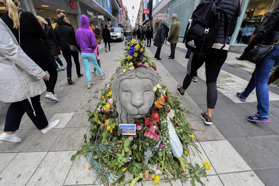 epa05904497 People walk by floral tributes and greetings near the crime scene next to Ahlens department store in the pedestrian street Drottninggatan in central Stockholm, Sweden, 12 April 2017. A hijacked beer truck ploughed into pedestrians on Drottninggatan in the Swedish capital and crashed into a department store, killing four people, injuring 15 others late 07 April 2017. EPA/FREDRIK SANDBERG SWEDEN OUT