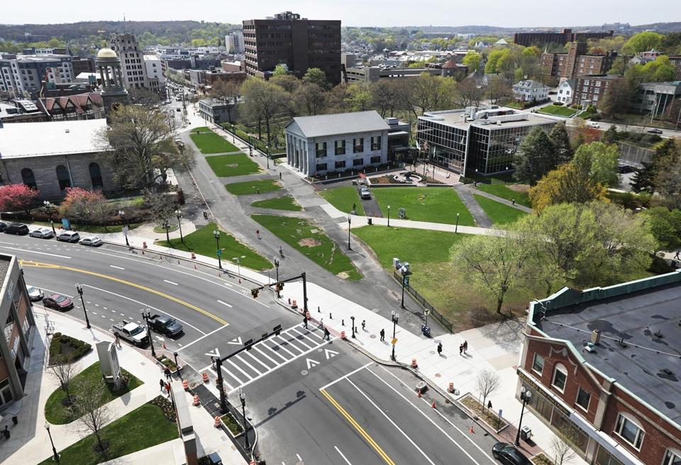Quincy, MA--4/28/2017 - Pedestrians traverse near the promenade of The Hancock Adams Green (cq). Hancock Street, foreground, used to run between United First Parish Church (cq), left, and Old Town Hall (cq), right, now the McIntyre Government Center (cq). Center right is the new City Hall. Quincy Center has seen a revival, with a redo of Hancock Street, construction of an apartment complex and new restaurants. Photo by Pat Greenhouse/Globe Staff Topic: 051417quincy Reporter: Timothy Logan