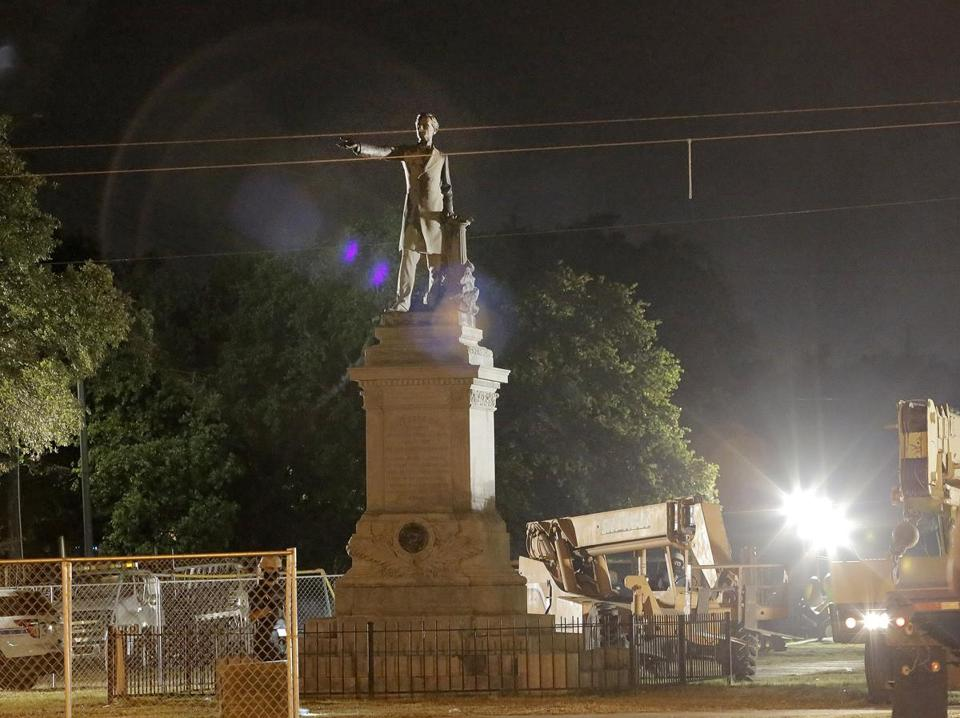 epa05956980 The statue of Confederate President Jefferson Davis is prepared for removal in the early morning hours in New Orleans, Louisiana, USA, 11 May 2017. The statue is the second of four monuments the city of New Orleans is removing following several court cases after the city decide the statues did not 'appropriately reflect the values of diversity and inclusion that make New Orleans strong today.' The process took over four hours with streets blocked in a four block radius with a heavy police presence as protesters both for and against the removal deomonstrated. EPA/DINAH ROGERS