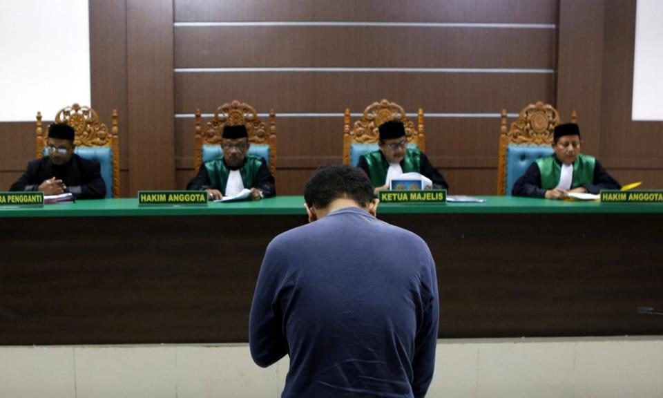 A man on trial for being in a same-sex relationship reacts as he listens to the judge at the Sharia court in Banda Aceh.