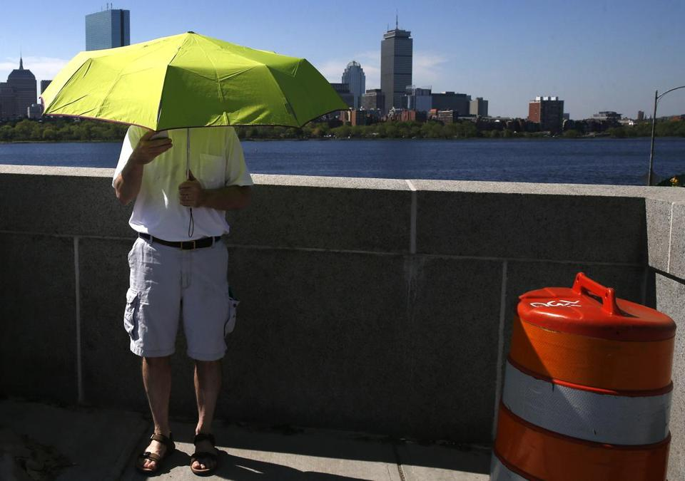 A man paused to check his phone along the Longfellow Bridge as he shielded himself from the sun Thursday.