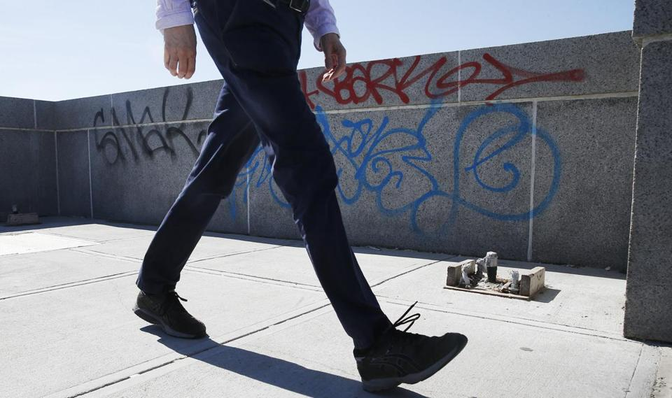 A man walked past graffiti on the Longfellow Bridge in Boston.
