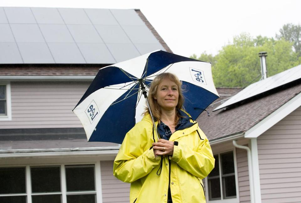 May 25, 2017 - Irene Kneeland poses with the solar panels on the roof of her home in Sutton, Mass. Kneeland expects to have an electric bill at nearly zero this year thanks to the panels. Photo Credit: Justin Saglio for the Boston Globe. Section: Business. Slug: 29solar.