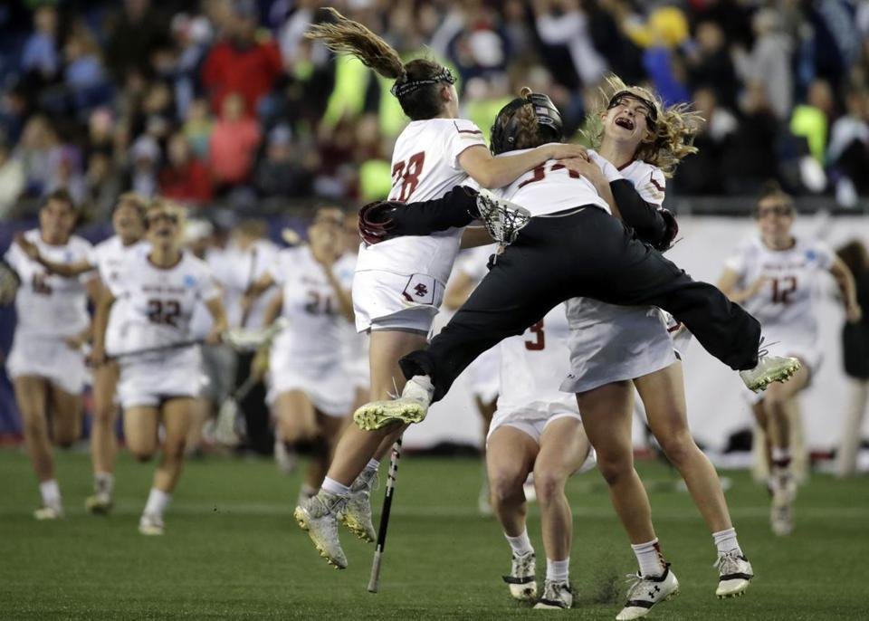 Boston College goalkeeper Lauren Daly (34) jumps to hug teammates Brooke Troy (28) and Carly Bell, right, after they defeated Navy 16-15 in an NCAA college Division 1 lacrosse semifinal, Friday, May 26, 2017, in Foxborough, Mass. Boston College will advance to the Championship final against Maryland. (AP Photo/Elise Amendola)