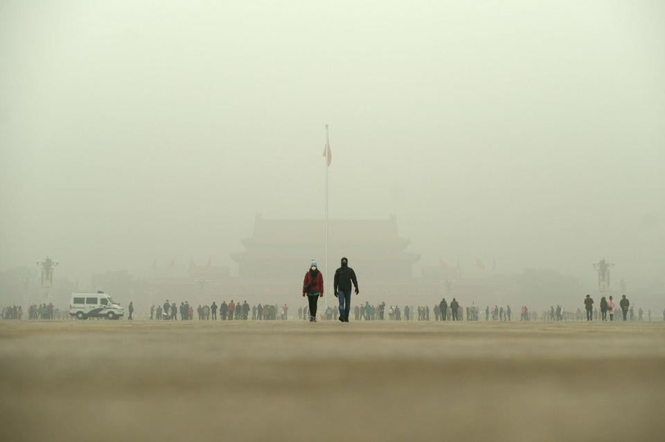 A man (R) and a woman wear masks as they walk in Tiananmen Square during heavy pollution in Beijing on December 1, 2015. Beijing ordered hundreds of factories to shut and allowed children to skip school as choking smog reached over 25 times safe levels on December 1, casting a cloud over China's participation in Paris climate talks. AFP PHOTO / WANG ZHAOWANG ZHAO/AFP/Getty Images