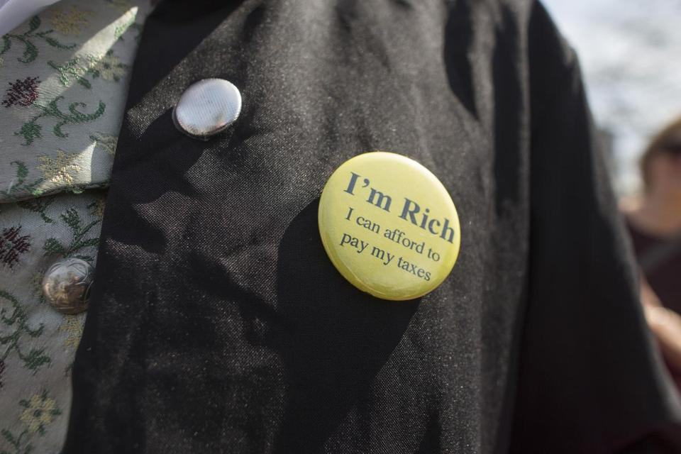 "CAMBRIDGE, MA - APRIL 15: A man wears a pin that reads ""I'm Rich, I Can Afford To Pay My Taxes"" during a Tax Day protest on April 15, 2017 in Cambridge, Massachusetts. Activists in cities across the nation are marching today to call on President Trump to release his tax returns. (Photo by Scott Eisen/Getty Images)"