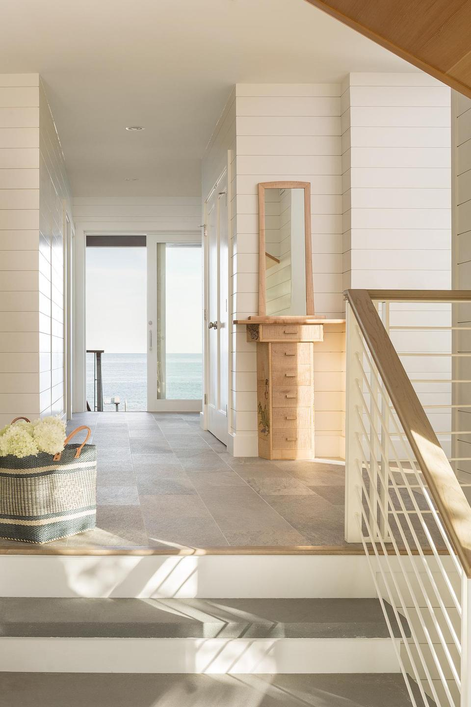 "Walter Zanger ""Walks"" tiles in gray textured porcelain connect the front entry to the back porch. The material helps keep water and sand from straying onto the wood-plank floors in the main living space."