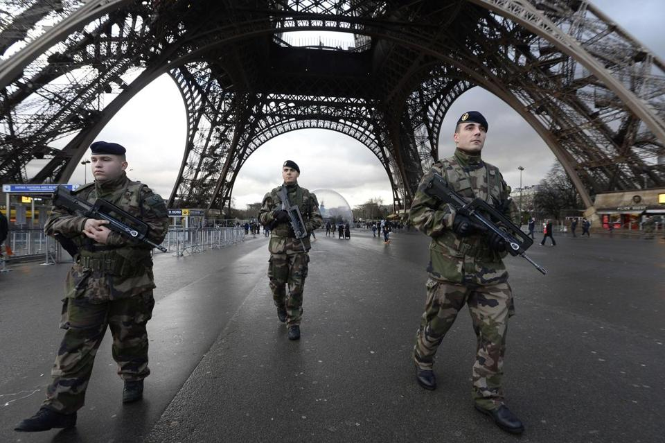 TOPSHOTS French soldiers patrol in front of the Eiffel Tower on January 8, 2015 in Paris as the capital was placed under the highest alert status a day after heavily armed gunmen shouting Islamist slogans stormed French satirical newspaper Charlie Hebdo and shot dead at least 12 people in the deadliest attack in France in four decades. A huge manhunt for two brothers suspected of massacring 12 people in an Islamist attack at a satirical French weekly zeroed in on a northern town Thursday after the discovery of one of the getaway cars. As thousands of police tightened their net, the country marked a rare national day of mourning for Wednesday's bloodbath at Charlie Hebdo magazine in Paris, the worst terrorist attack in France for half a century. AFP PHOTO / BERTRAND GUAYBERTRAND GUAY/AFP/Getty Images