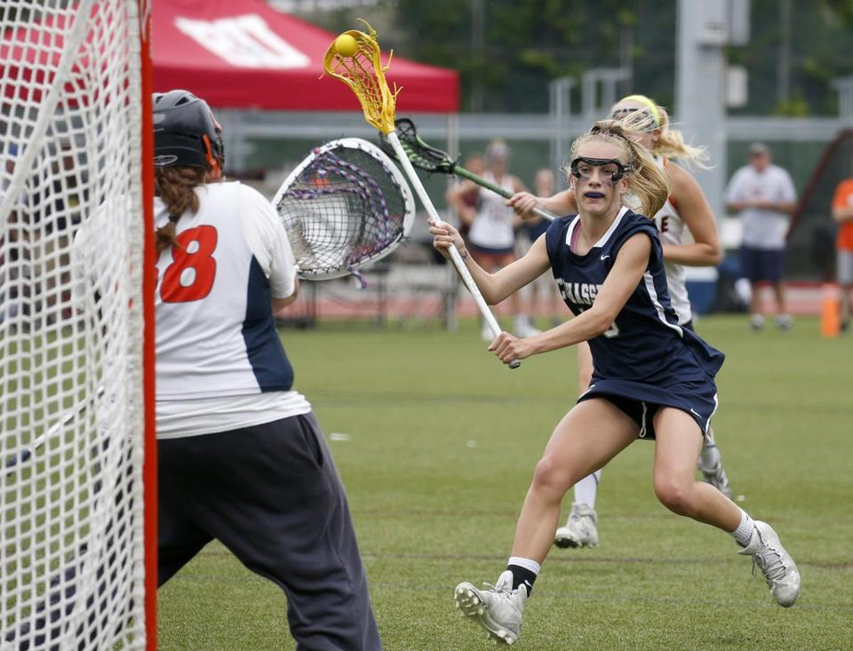 Boston, MA: 6/17/17 Cohasset's Jane Hansen scores past Walpole goalie Morgan Fortana during the second half of the Division 2 MIAA lacrosse state championship. Photo/Mary Schwalm for The Boston Globe (18hslacrosse)