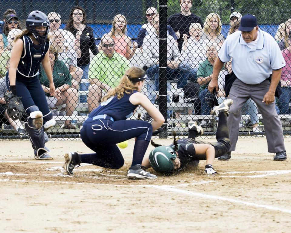 Grafton's Elisabeth Sudbey slides headfirst into home plate to score what proved to be the winning run as Dracut pitcher Ryley White loses the ball while attempting to make the tag.